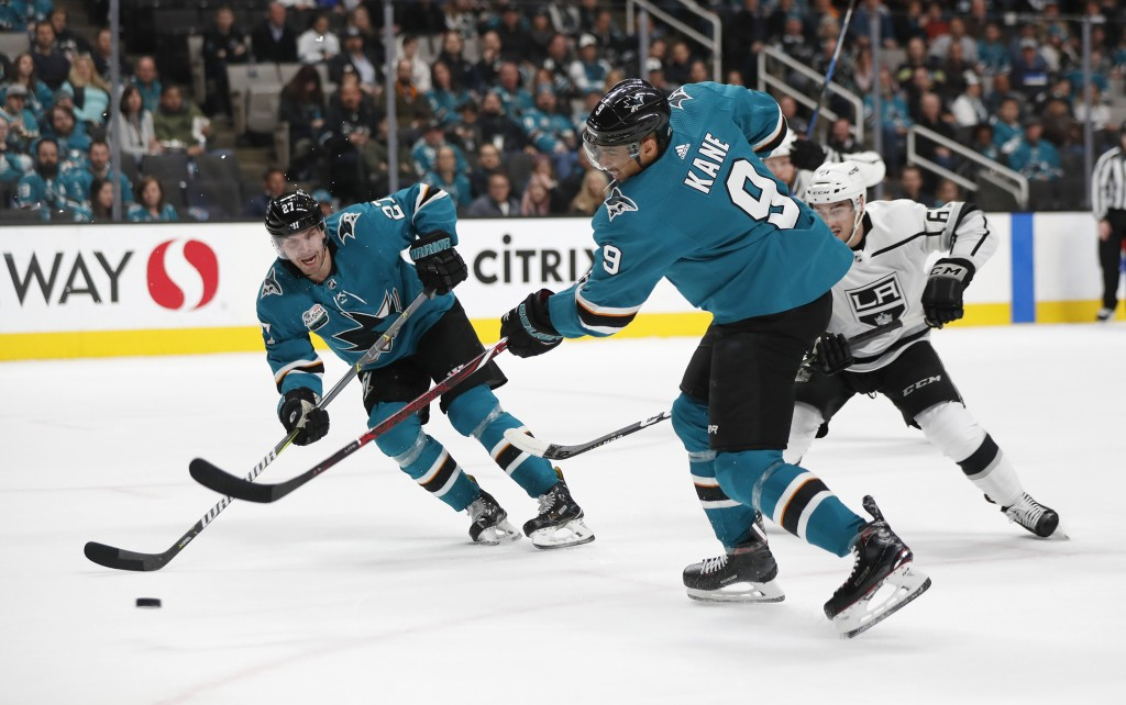 San Jose Sharks' Evander Kane (9) fires the puck as Joonas Donskoi (27), skates to the net for a rebound goal against the Los Angeles Kings in the fir