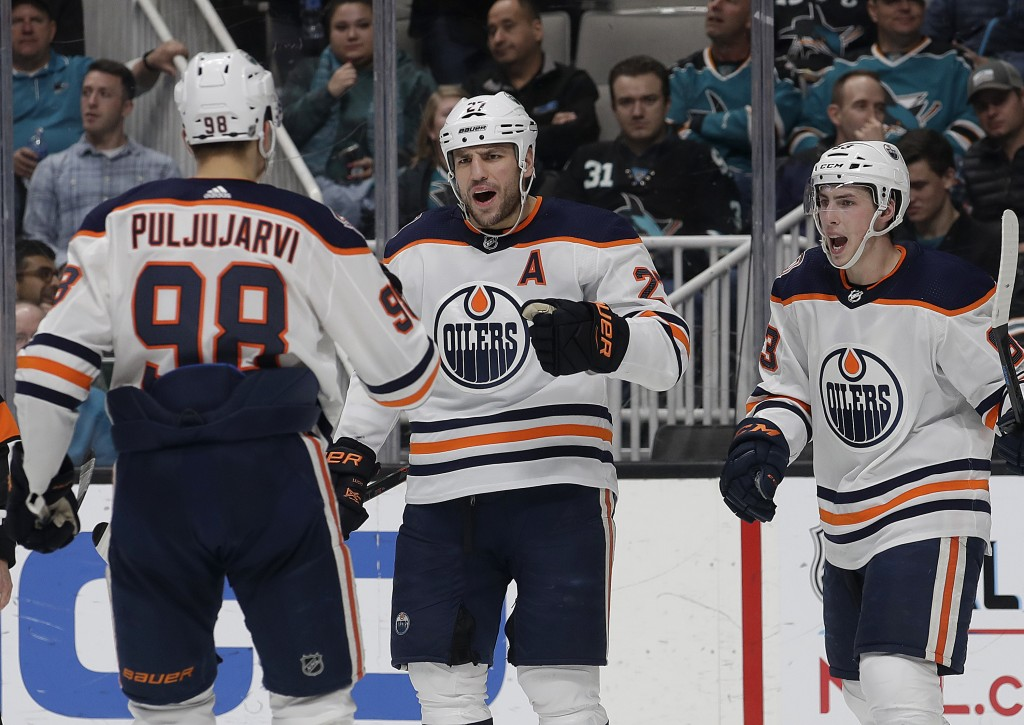 Edmonton Oilers left wing Milan Lucic, center, is congratulated by right wing Jesse Puljujarvi (98), from Sweden, and center Ryan Nugent-Hopkins (93)