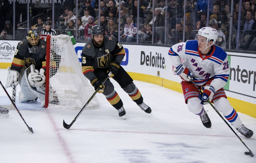 New York Rangers left wing Jimmy Vesey looks for a pass while being defended by Vegas Golden Knights defenseman Deryk Engelland during the first perio