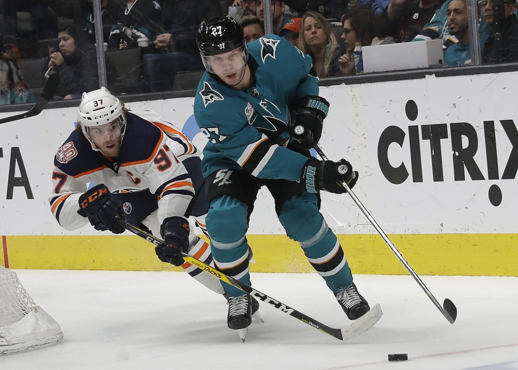 Edmonton Oilers center Connor McDavid, left, reaches for the puck next to San Jose Sharks right wing Joonas Donskoi (27), from Finland, during the sec