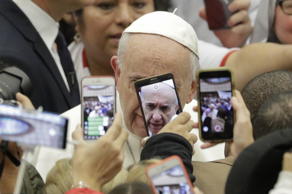 Pope Francis is framed by cellphones as he arrives for his weekly general audience, in the Pope Paul VI hall, at the Vatican, Wednesday, Jan. 9, 2019....