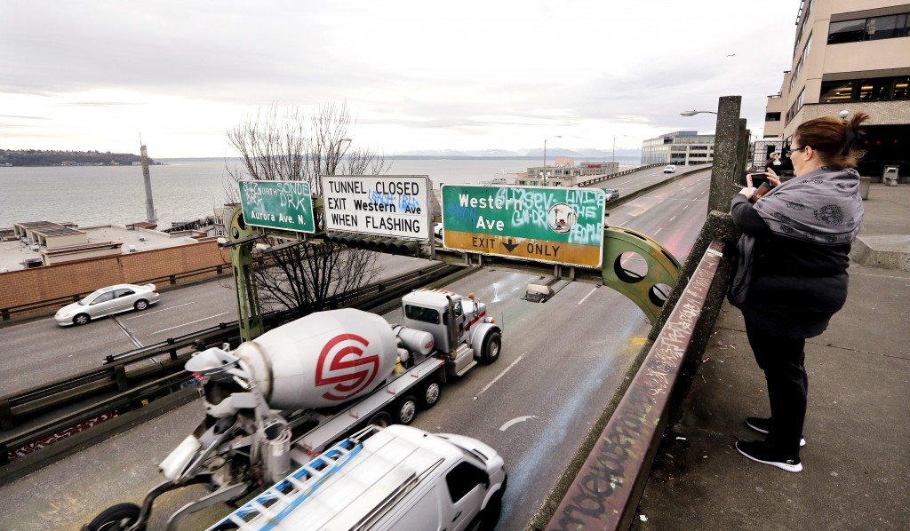 In this photo taken Wednesday, Jan. 2, 2019, a woman takes a photo toward Elliott Bay as Alaskan Way Viaduct traffic rolls past her below ahead of an ...