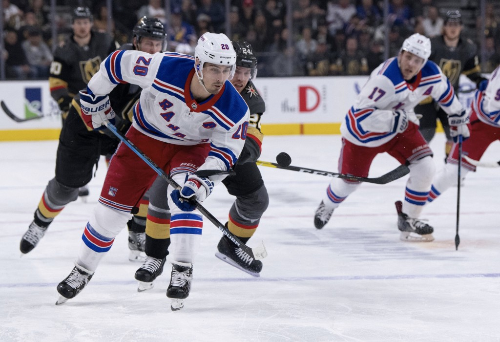 New York Rangers left wing Chris Kreider and Vegas Golden Knights center Oscar Lindberg battle for the puck during the first period of an NHL hockey g