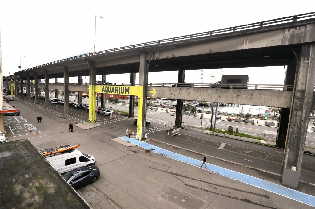 In this photo taken Wednesday, Jan. 2, 2019, pedestrians walk nearby and traffic continues on the double-decker Alaskan Way Viaduct overhead, before a...
