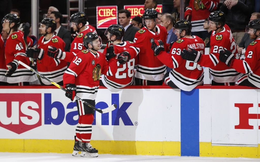 Chicago Blackhawks left wing Alex DeBrincat celebrates with teammates after scoring against the Nashville Predators during the first period of an NHL ...