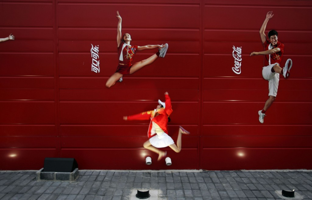FILE - In this Aug. 20, 2008 file photo, a young girl mimics the pose of a Chinese Olympic athletes depicted in Coca-Cola advertising, at the Olympic