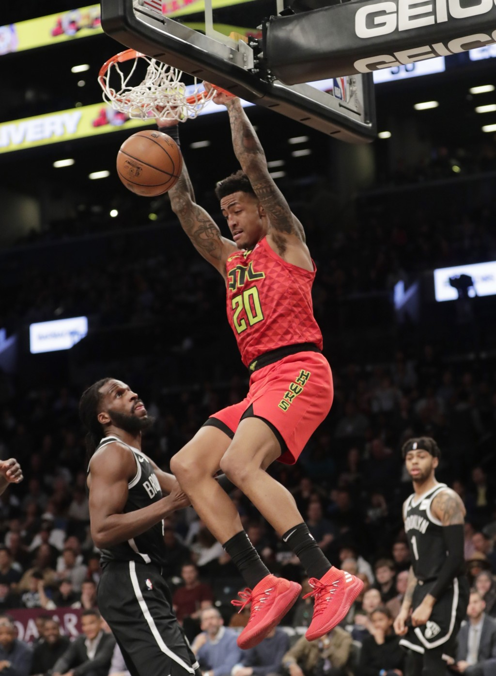 Atlanta Hawks' John Collins (20) dunks in front of Brooklyn Nets' DeMarre Carroll (9) during the first half of an NBA basketball game Wednesday, Jan. ...