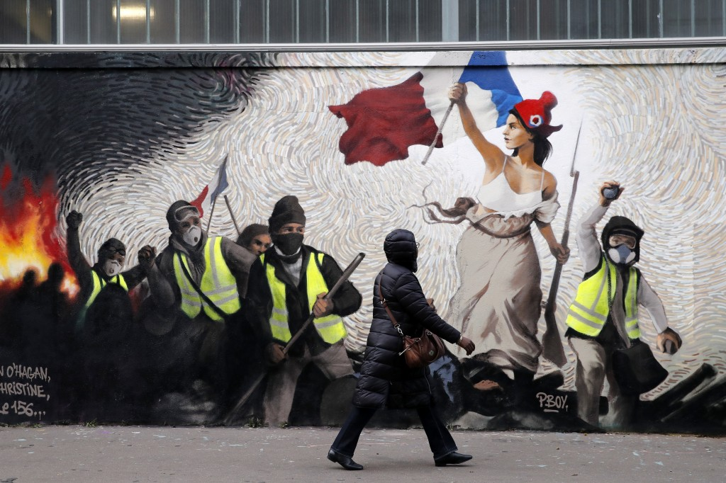 "A woman passes by a mural by street artist PBOY depicting Yellow Vest (gilets jaunes) protestors inspired by a painting by Eugene Delacroix, ""La Liber"