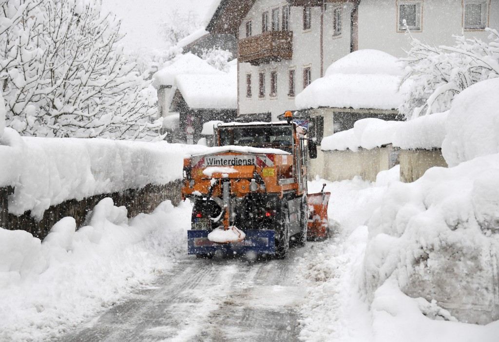 A snow plough cleans a street in Berchtesgaden, southern Germany, Thursday, Jan. 10, 2019 after large parts of southern Germany and Austria were hit b