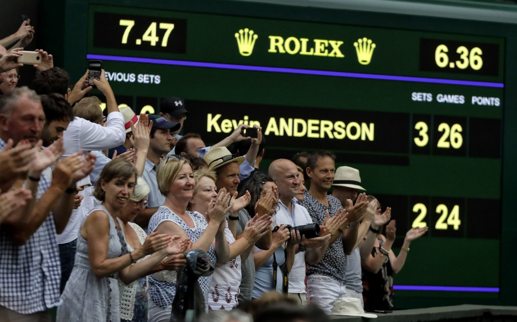 FILE - In this July 13, 2018, file photo, spectators applaud as the scoreboard displays the final score in the men's singles semifinals match in which