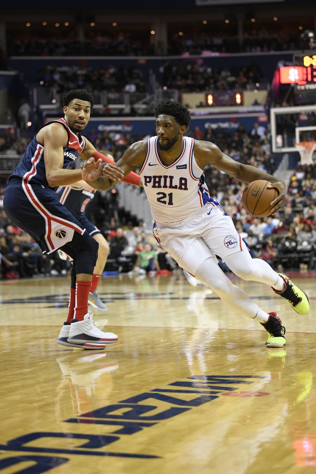 Philadelphia 76ers center Joel Embiid (21) dribbles the ball against Washington Wizards forward Otto Porter Jr., left, during the first half of an NBA