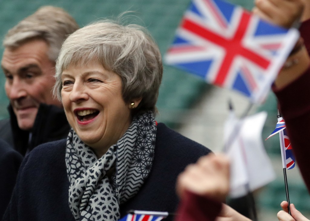 Britain's Prime Minister Theresa May reacts ashildren play rugby, during a visit with Japanese Prime Minister Shinzo Abe to Twickenham Rugby Stadium,