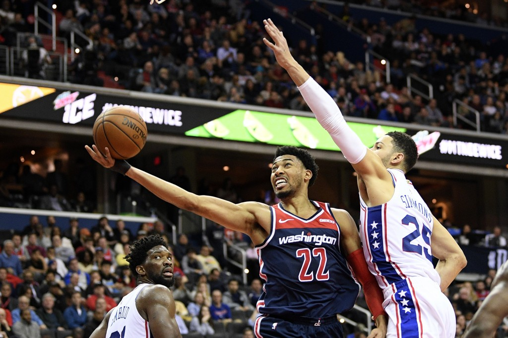 Washington Wizards forward Otto Porter Jr. (22) goes to the basket against Philadelphia 76ers guard Ben Simmons (25) and center Joel Embiid, left, dur...