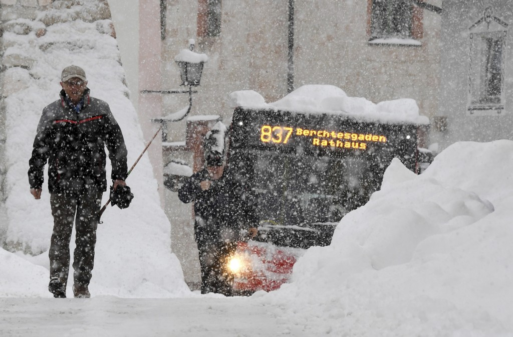 A man and a bus make their way on a street in Berchtesgaden, southern Germany, Thursday, Jan. 10, 2019 after large parts of southern Germany and Austr