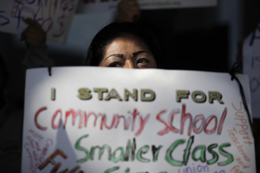 Manuela Panjoj, 42-year-old mother of five children, holds a sign during a news conference outside the Los Angeles Unified School District headquarter