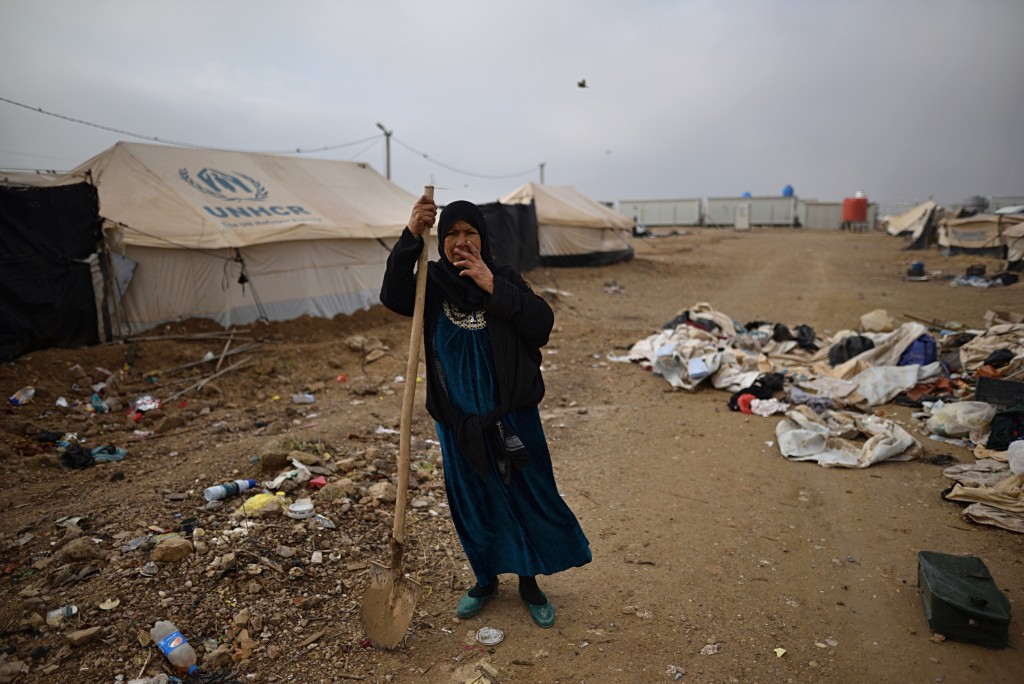 In this Dec. 26, 2018 photo, a displaced woman cleans in Bzeibiz camp, Anbar province, Iraq. A little over a year since the country fought its last ba