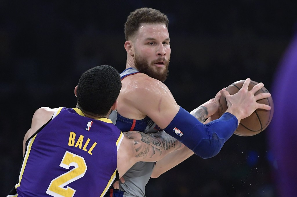 Los Angeles Lakers guard Lonzo Ball, left, reaches for the ball held by Detroit Pistons forward Blake Griffin during the first half of an NBA basketba...