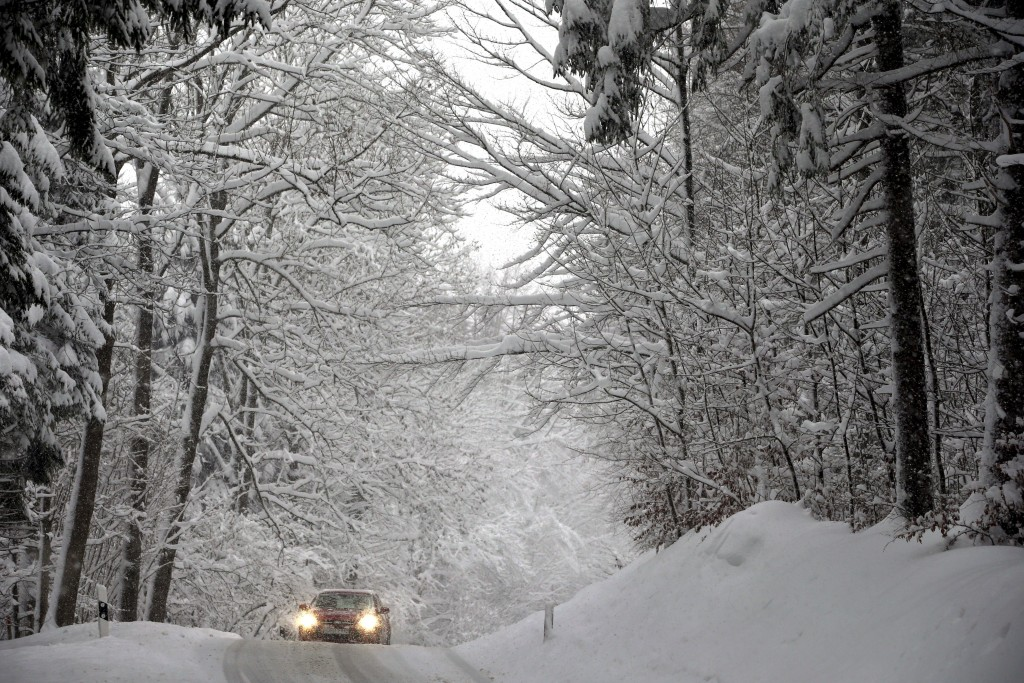 A car drives on a road through a forest in Schongau, southern Germany, Thursday, Jan. 10, 2019 after Austria and southern Germany were hit by heavy sn