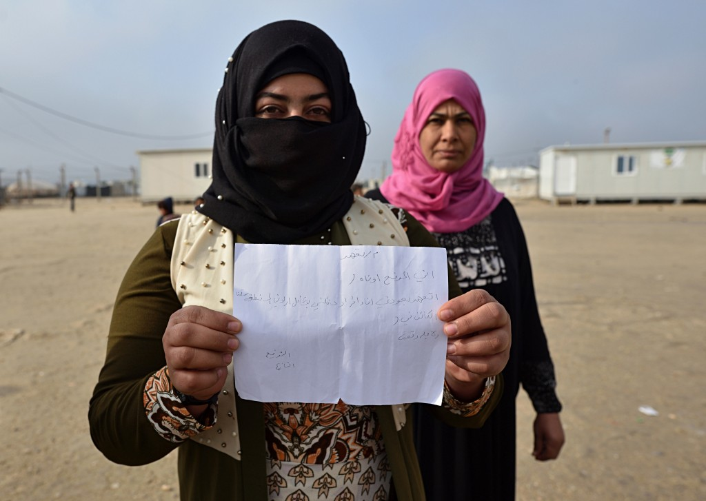 In this Dec. 26, 2018 photo, Khalwa Hamid, holds a facsimile of a handwritten form that says she is returning to her area of origin with her family, v