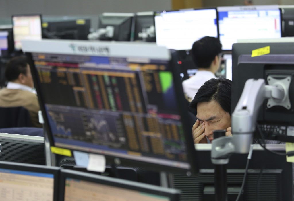 A currency trader talks on the phone at the foreign exchange dealing room of the KEB Hana Bank headquarters in Seoul, South Korea, Thursday, Jan. 10, ...