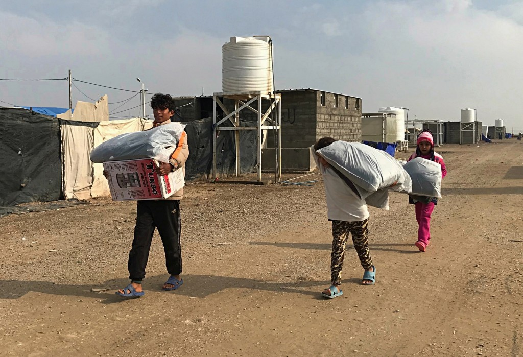 In this Dec. 26, 2018 photo, displaced people carry humanitarian aid at the Amariyat al-Fallujah camp, in Anbar province, Iraq. A little over a year s