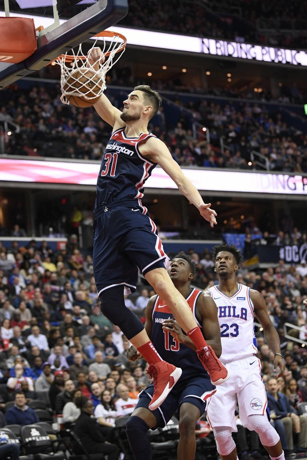 Washington Wizards guard Tomas Satoransky (31), of the Czech Republic, dunks past Philadelphia 76ers guard Jimmy Butler (23) during the second half of...