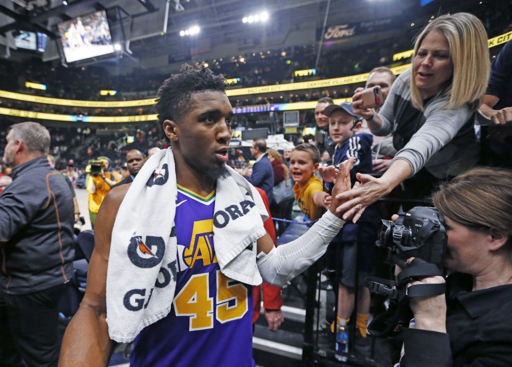 A fan reaches for Utah Jazz guard Donovan Mitchell (45) as he walks off the court following the team's NBA basketball game against the Orlando Magic o...
