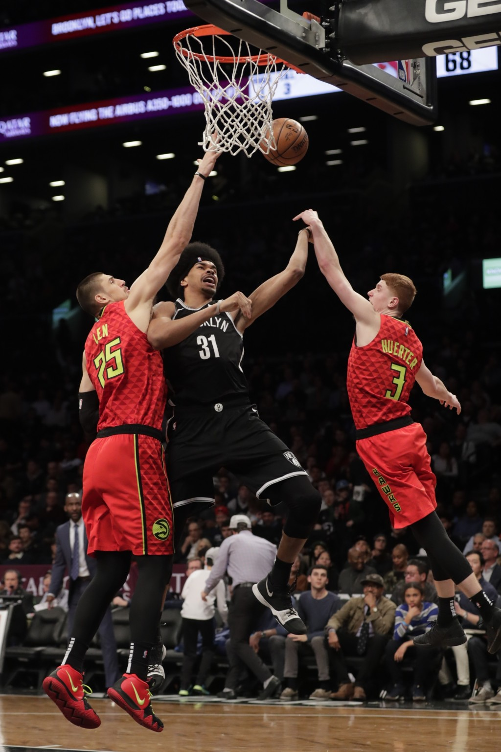 Atlanta Hawks' Alex Len (25) and Kevin Huerter (3) defend against Brooklyn Nets' Jarrett Allen (31) during the second half of an NBA basketball game W...