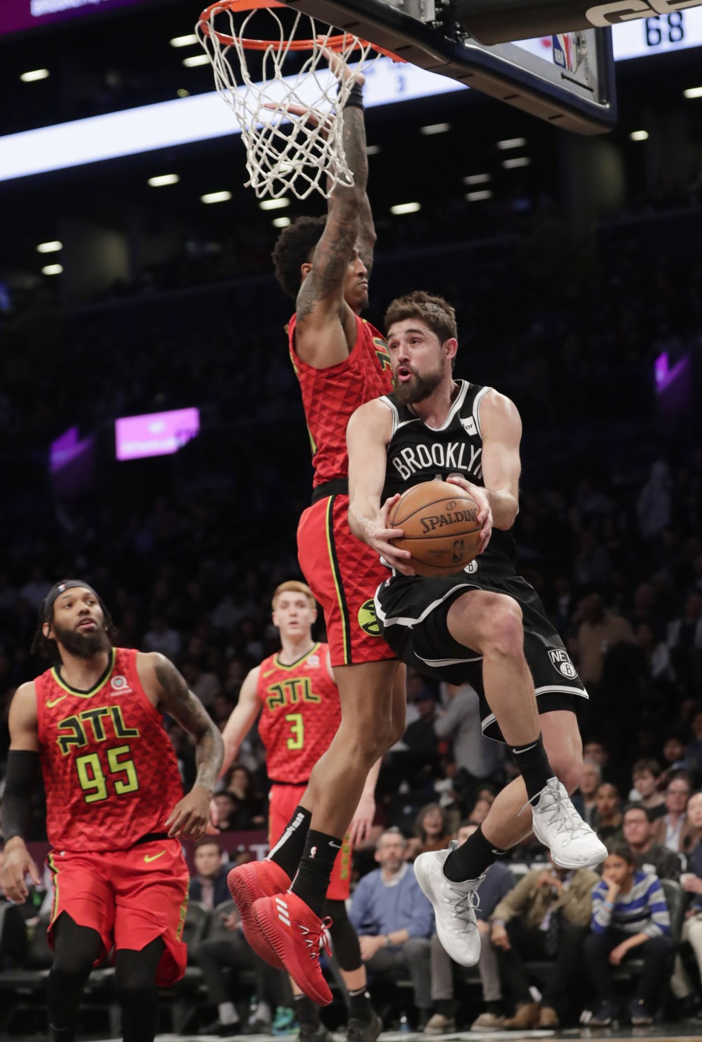 Brooklyn Nets' Joe Harris (12) looks to pass the ball as Atlanta Hawks' John Collins (20) defends during the second half of an NBA basketball game Wed...