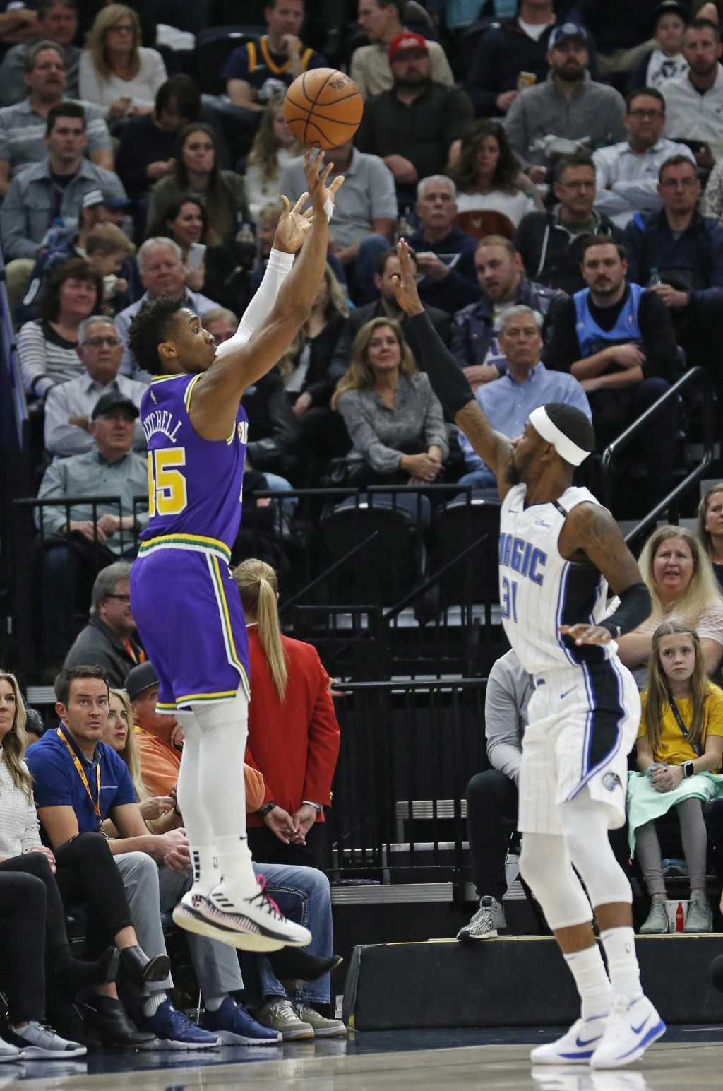 Utah Jazz guard Donovan Mitchell (45) shoots as Orlando Magic guard Terrence Ross (31) defends during the first half of an NBA basketball game Wednesd...