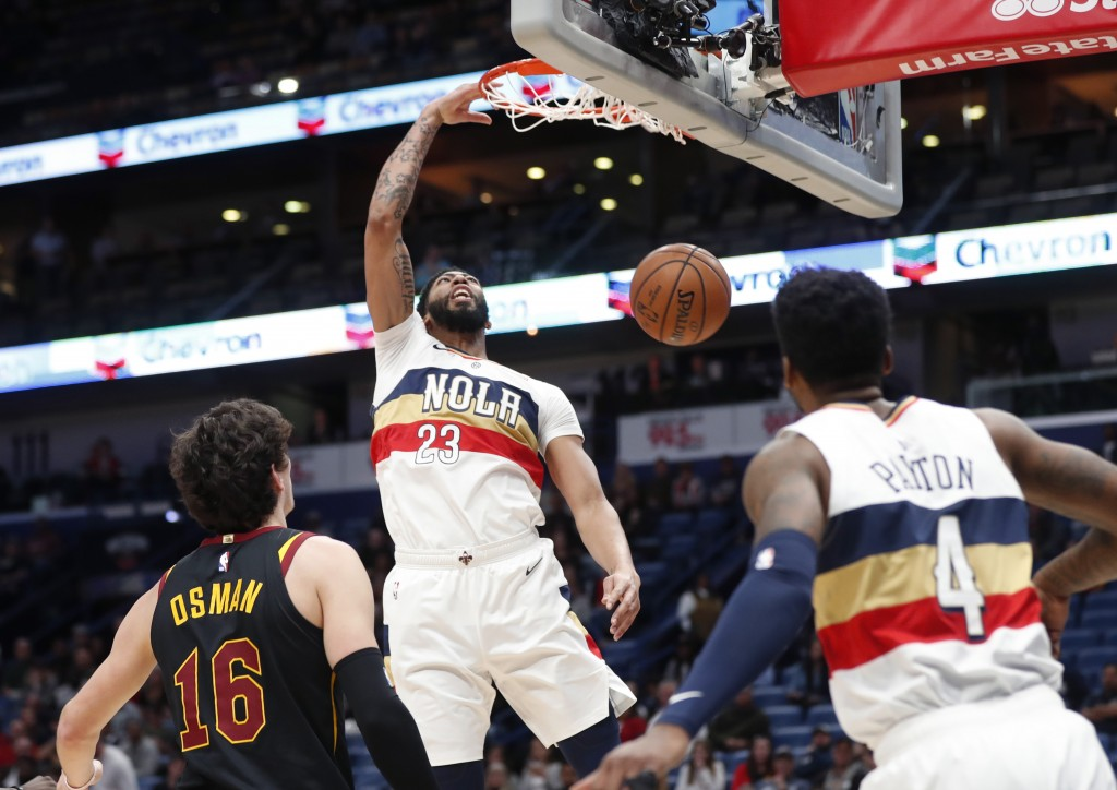 New Orleans Pelicans forward Anthony Davis (23) slam dunks over Cleveland Cavaliers forward Cedi Osman (16) in the first half of an NBA basketball gam