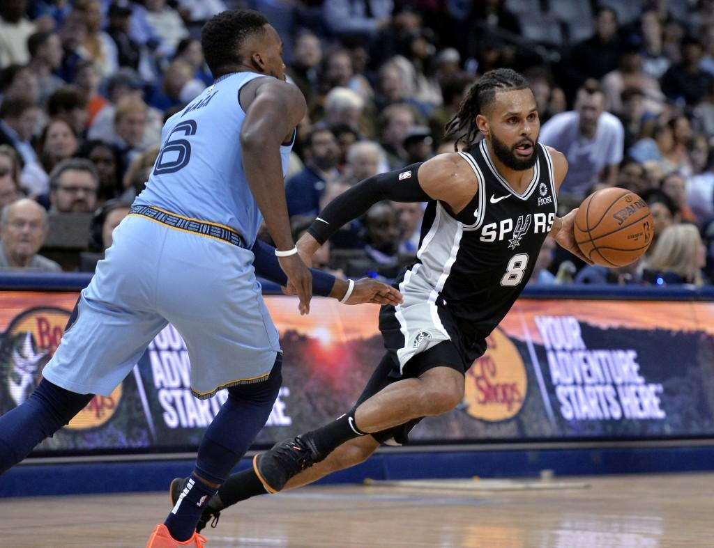 San Antonio Spurs guard Patty Mills (8) drives past Memphis Grizzlies guard Shelvin Mack (6) during the second half of an NBA basketball game Wednesda...
