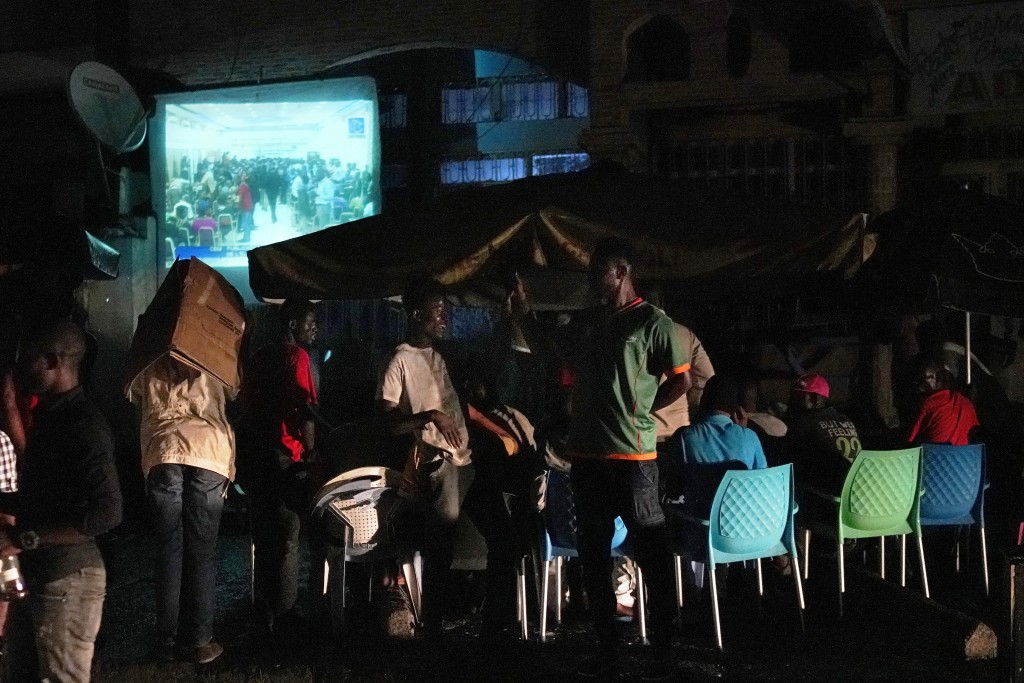 Kinshasa resident watch the preliminary results of the elections broadcast on a television in Kinshasa, Congo, Thursday Jan. 10, 2019. As Congo anxiou...