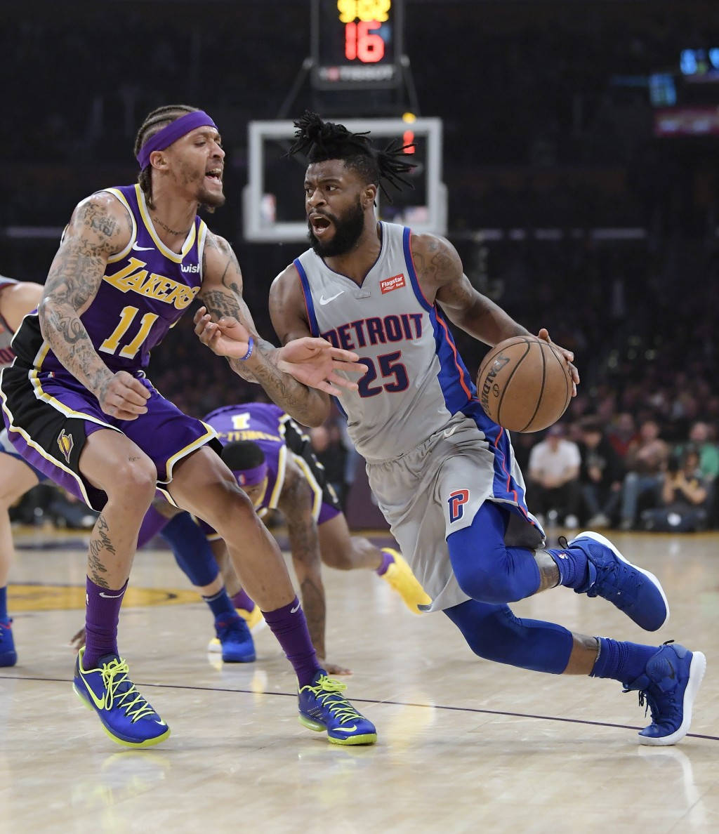 Detroit Pistons guard Reggie Bullock, right, tries to drive past Los Angeles Lakers forward Michael Beasley during the first half of an NBA basketball