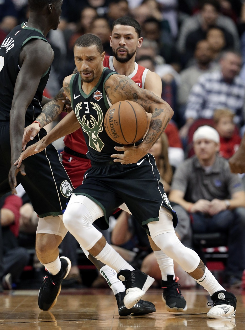 Milwaukee Bucks guard George Hill (3) bobbles the ball as he drives to the basket in front of Houston Rockets guard Austin Rivers, back, during the fi...
