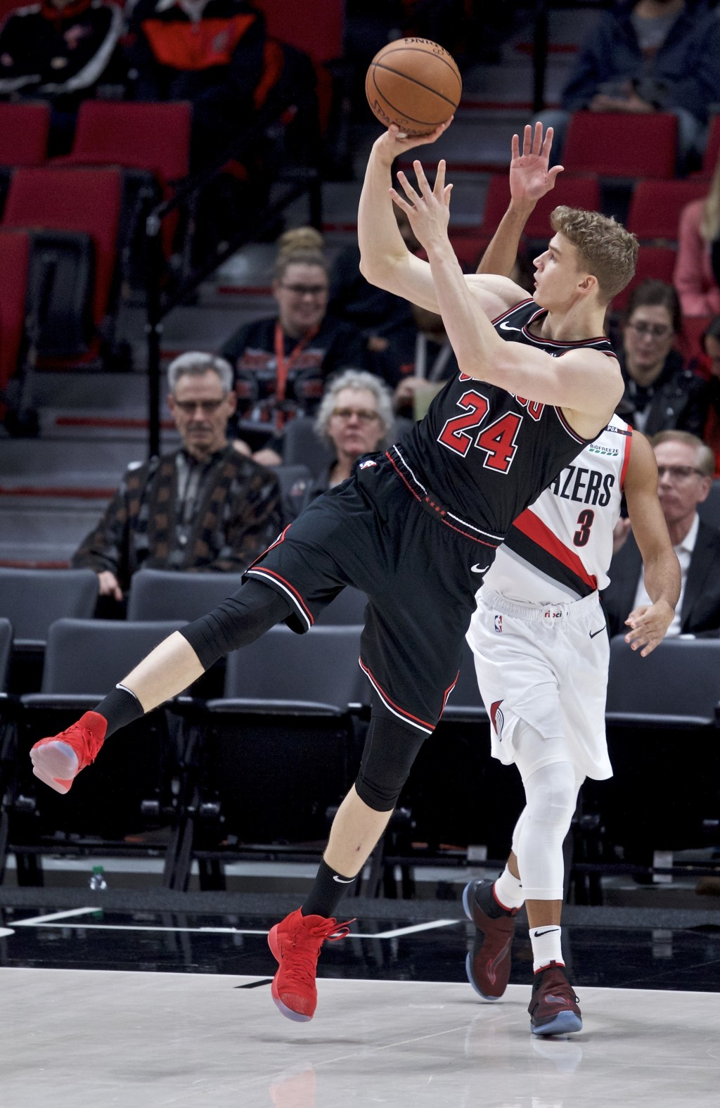 Chicago Bulls forward Lauri Markkanen, front, shoots over Portland Trail Blazers guard CJ McCollum during the first half of an NBA basketball game in ...