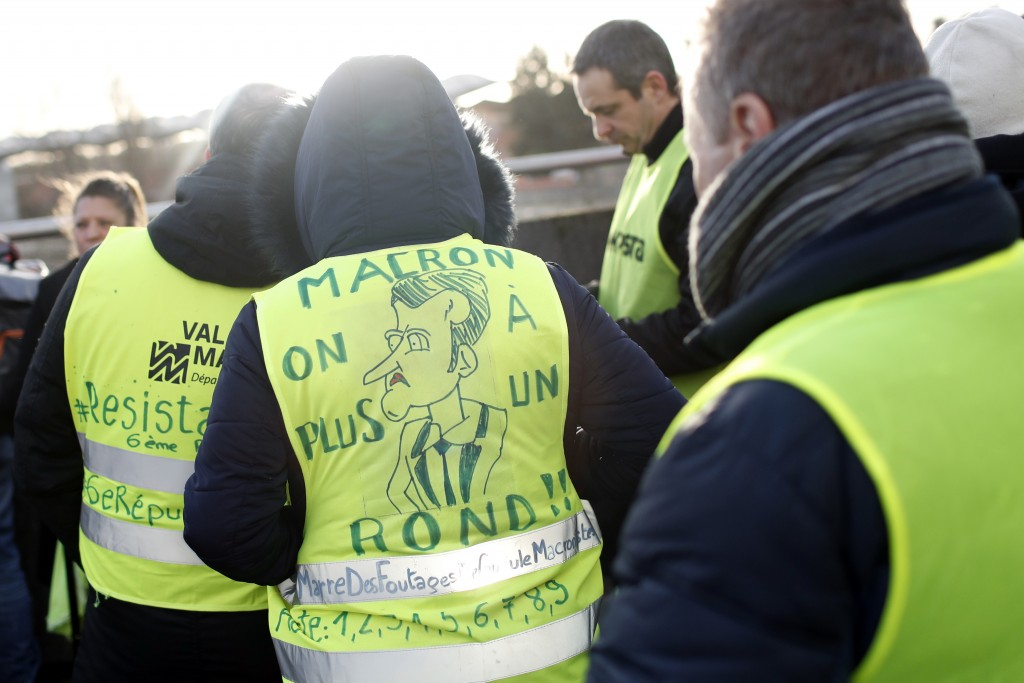 A protestor wears a yellow jacket reading
