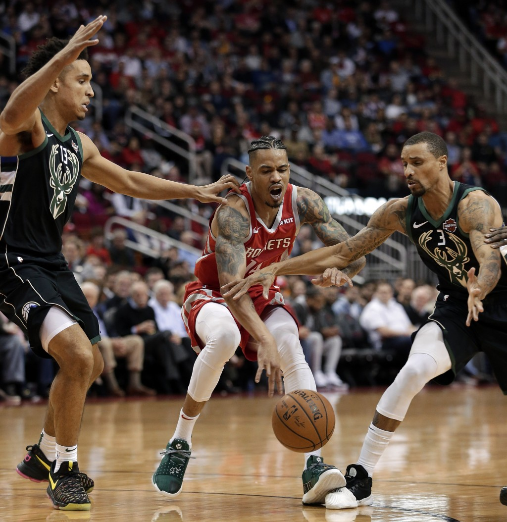 Houston Rockets guard Gerald Green, middle, loses the ball between Milwaukee Bucks guard Malcolm Brogdon (13) and guard George Hill (3) during the fir...