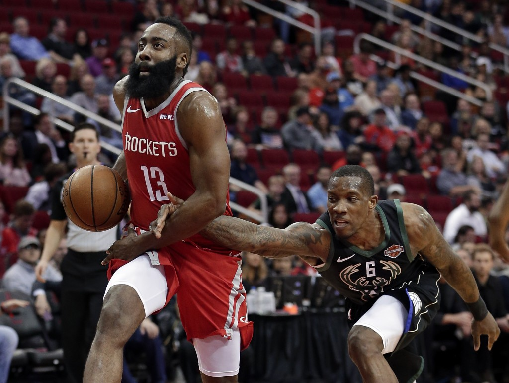 Houston Rockets guard James Harden (13) is fouled on a drive to the basket by Milwaukee Bucks guard Eric Bledsoe (6) during the first half of an NBA b...