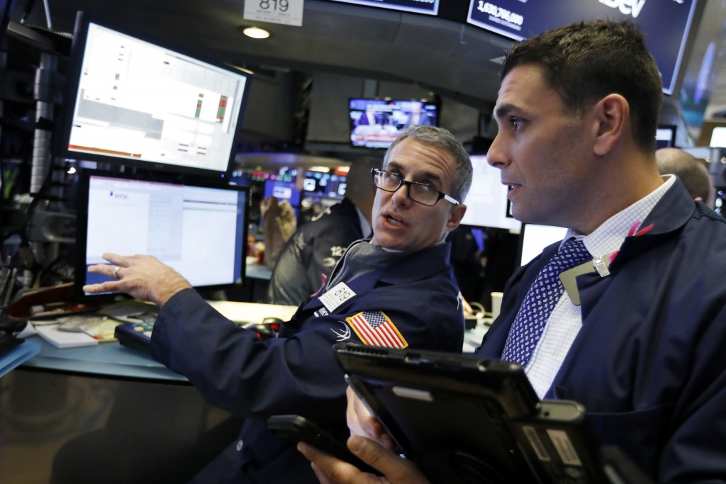 FILE- In this Jan. 3, 2019, file photo specialist Anthony Rinaldi, left, works at his post on the floor of the New York Stock Exchange. The U.S. stock