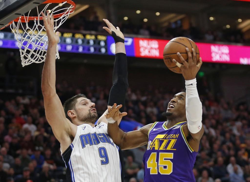 Utah Jazz guard Donovan Mitchell (45) goes to the basket as Orlando Magic center Nikola Vucevic (9) defends during the second half of an NBA basketbal...
