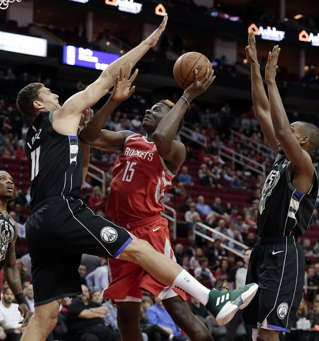 Houston Rockets center Clint Capela (15) puts up a shot between Milwaukee Bucks center Brook Lopez (11) and Milwaukee Bucks forward Khris Middleton, r...