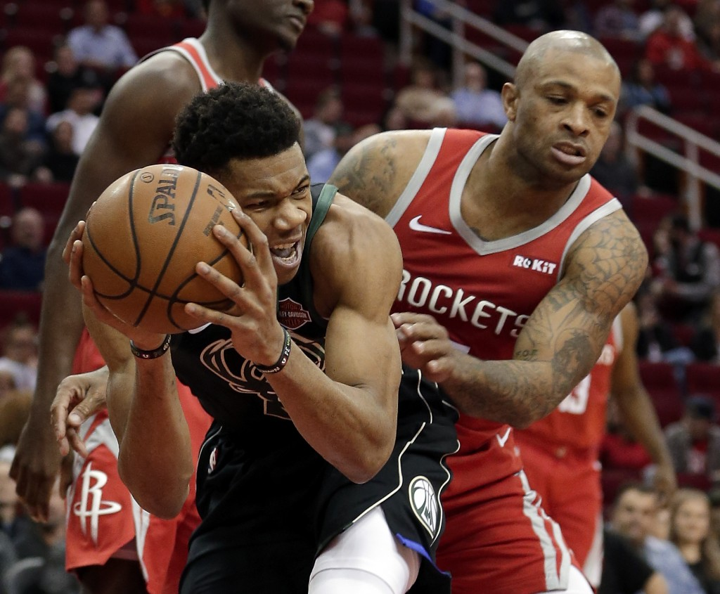 Milwaukee Bucks forward Giannis Antetokounmpo, left, protects his rebound from Houston Rockets forward PJ Tucker, right, during the first half of an N...