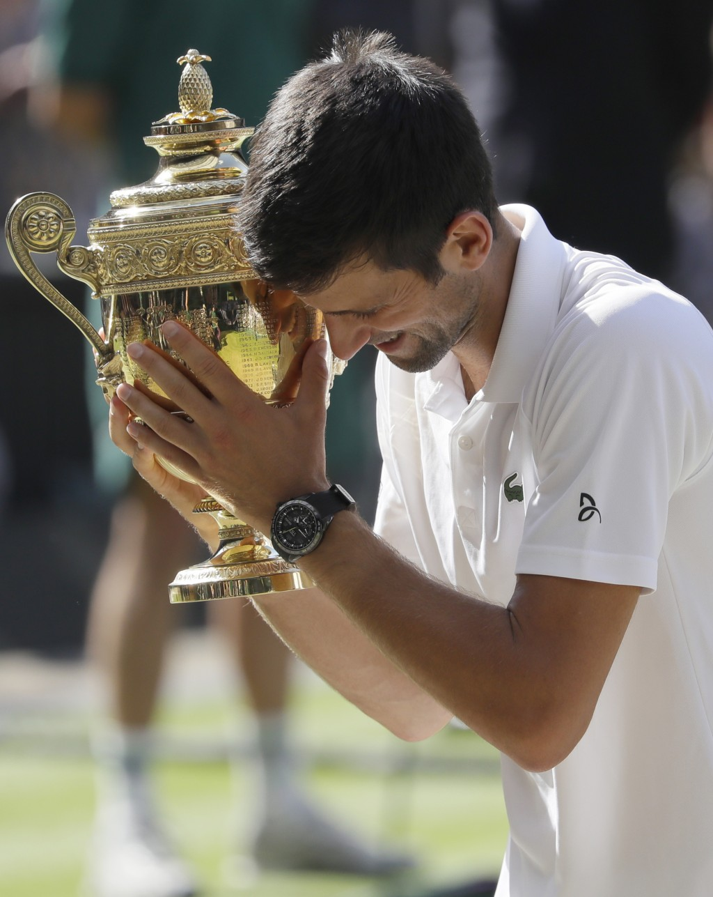 FILE - In this July 15, 2018, file photo, Serbia's Novak Djokovic holds the trophy after winning the men's singles final match against Kevin Anderson