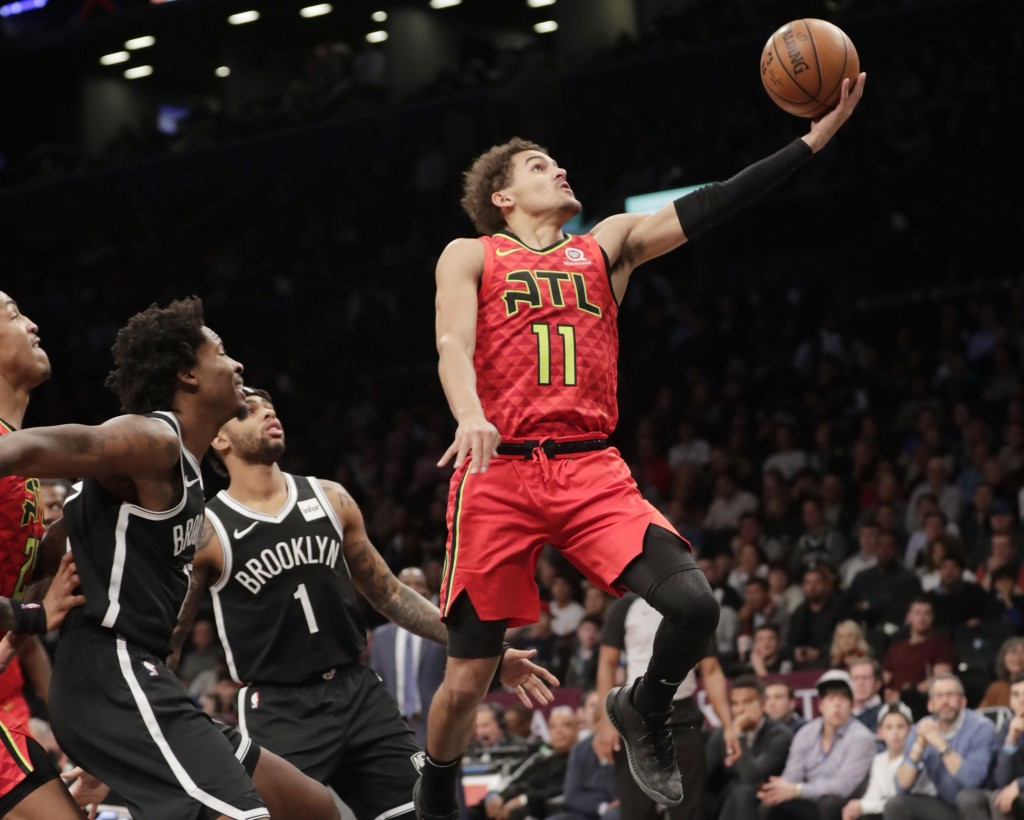 Atlanta Hawks' Trae Young (11) drives past Brooklyn Nets' D'Angelo Russell (1) during the first half of an NBA basketball game Wednesday, Jan. 9, 2019
