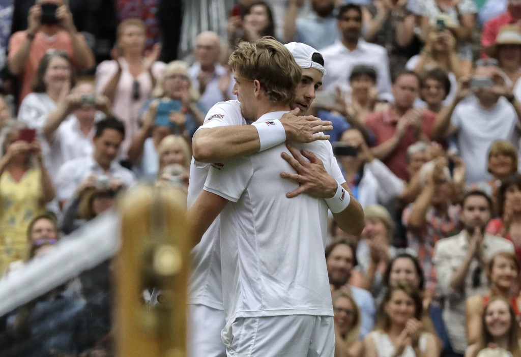 FILE - In this July 13, 2018, file photo, South Africa's Kevin Anderson hugs John Isner of the United States, right, after defeating him in their men'