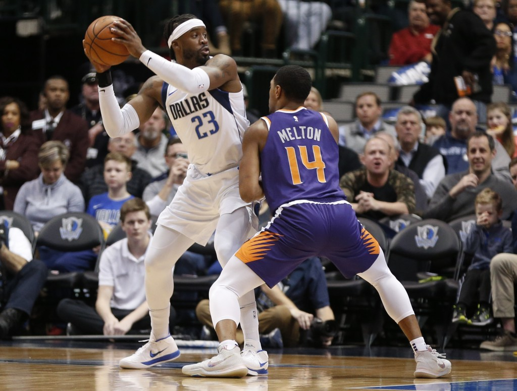 Dallas Mavericks guard Wesley Matthews (23) looks to pass around Phoenix Suns guard De'Anthony Melton (14) during the first half of an NBA basketball ...