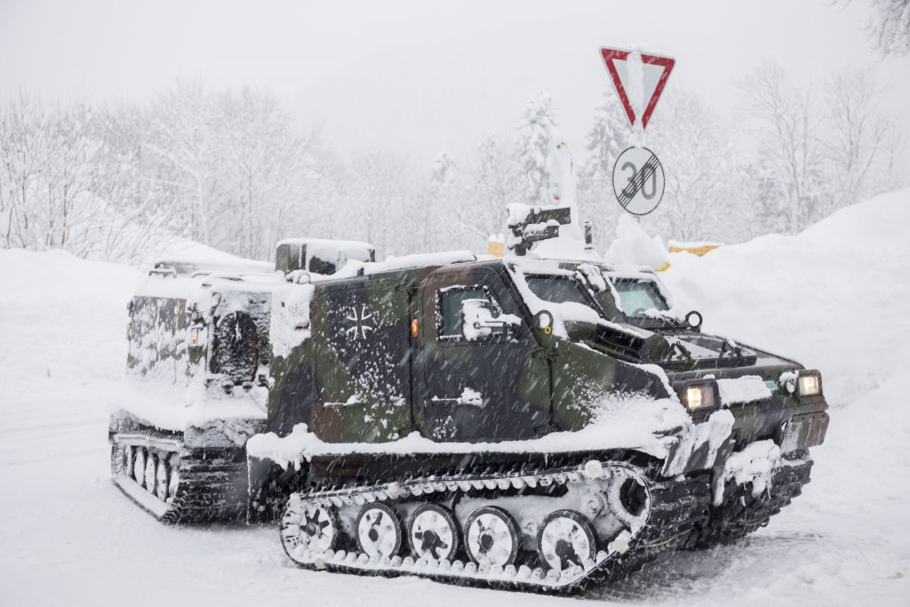 A track vehicle of the German army provides food to a village near Berchtesgaden, southern Germany, Thursday, Jan. 10, 2019 after southern Germany and