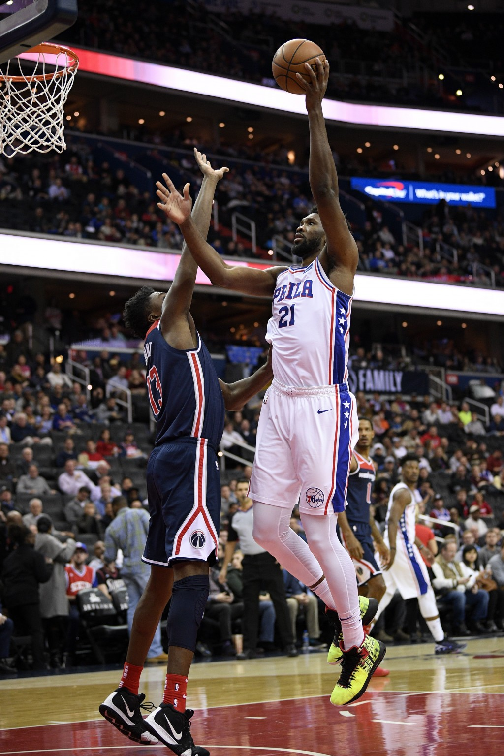 Philadelphia 76ers center Joel Embiid (21) goes to the basket against Washington Wizards center Thomas Bryant (13) during the first half of an NBA bas...