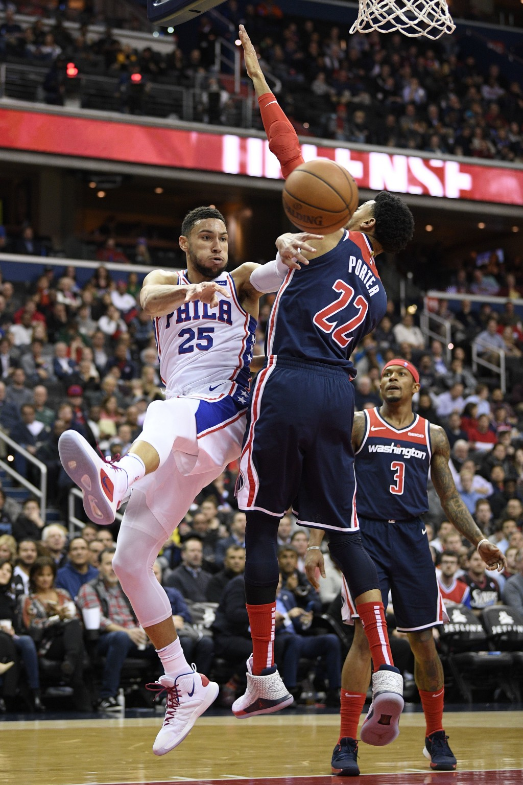 Philadelphia 76ers guard Ben Simmons (25) passes the ball against Washington Wizards forward Otto Porter Jr. (22) and guard Bradley Beal (3) during th